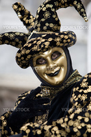A joker at the Venice carnival in St. Marc's Square in a gold and black costume