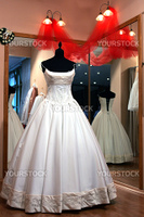 Traditional white wedding dress on display in windowed dressing room.