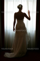 Rear view of young bride in white wedding dress looking out of window.