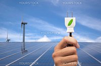 ECO power concept.hand holding green power plug and solar panel and wind turbine background