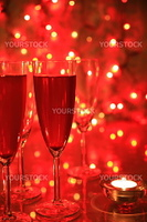 Champagne in glasses on red background with twinkle lights