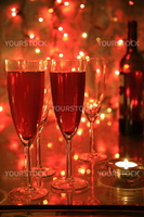 Champagne on red background with blured lights.