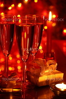 Champagne in glasses and gift boxes on red background with blured lights