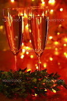 Champagne in glasses with green box twig an d blured lights on background.