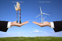 pollution and clean energy concept. businessman holding windmills and refinery with air pollution