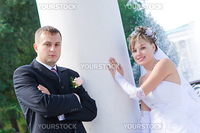 a bride and a groom stand by a white column