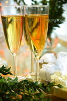 Close-up of glasses with champagne, gift boxes and green twig of box.