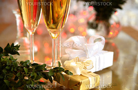 Champagne in glasses, green twig and gift boxes.