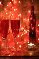 Champagne in glasses, candlelights and blured lights on red background