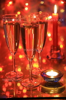 Champagne in glasses, candle and blured lights on red background