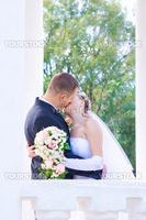 a bride and a groom kiss in the columns