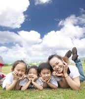 happy asian family on the grass with cloud background