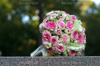 The forgotten wedding bouquet from roses lays on a granite stone
