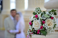 Wedding bouquet against the groom and the bride