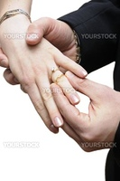 Groom placing ring on finger of bride at wedding isolated over white