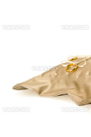 A pair of gold wedding bands tied to a ring pillow made of champagne-colored duchess satin with cream beadwork detail.