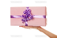 A box tied with a violet satin ribbon bow. A gift for Christmas, Birthday, Wedding, or Valentine's day.