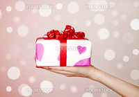 A box tied with a red satin ribbon bow. A gift for Christmas, Birthday, Wedding, or Valentine's day.