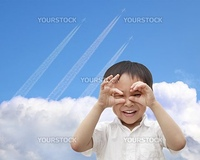 happy boy watching airplane flying through the sky over the cloud