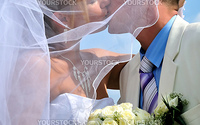 wedding passionative kiss of bride and groom under blue sky
