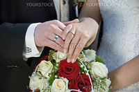 the bride and the groom showing their rings above the brides bouqet