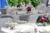 Close up of beautifully laid tables at wedding reception venue, focus on bouquet of flowers.