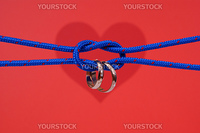 connected strings with golden wedding rings on red background