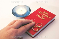 hand on a bible and rings with a candle