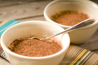 Tiramisu with a spoon on a wooden table with a colorful placemat