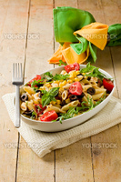 photo of delicious tasty pasta salad on wooden table with fresh vegetables