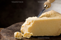 photo of delicious italian parmesan cheese with knife on wooden table