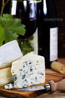 Three cheeses with a bottle and glass of red wine