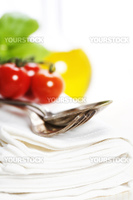 Spoon, fork, napkin and pasta ingredients (olive oil, basil, tomato)