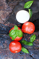 Ingredients for Caprese Salad. Mozzarella cheese, fresh basil, and tomatoes on a rustic slate background.