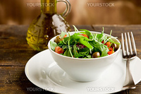 photo of deliciuos light salad with arugula and tomatoes in white bowl on wooden table