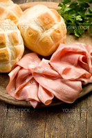 Sliced soft mortadella sausage on wooden table with bread