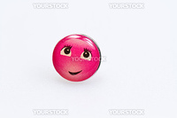 smiley character on metal thumbtack on white surface