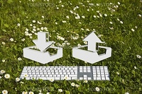 Downloading and uploading symbol and modern keyboard on green grass in garden