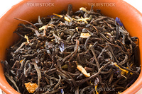 Dry green tea with slices of orange-peels and a bergamot in a clay bowl close up