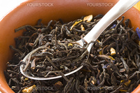 Dry green tea with slices of orange-peels and a bergamot in a clay bowl with spoon close up