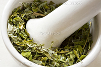 Dry leaves in a bowl in mortar with pestle close up