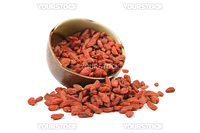 Red dry goji berries spilling out of a green and brown dish on a reflective white background