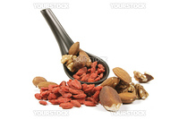 Red dry goji berries with mixed nuts on a small black spoon with a reflective white background
