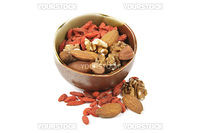 Red dry goji berries with mixed nuts in a green and brown bowl with on a reflective white background
