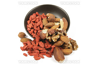 Red dry goji berries with mixed nuts spilling from a small black bowl on a reflective white background