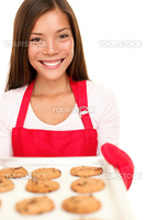 baking woman showing cookies on oven tray. Happy smiling mixed race Chinese Asian / white Caucasian cooking at home. Isolated on white background.