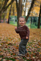 little beauty girl playing autumn yard withh yellow leafs