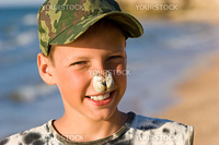 portrait series: a summer cheerful boy with sea shell