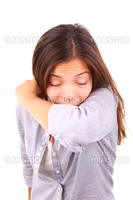 Woman having the flu and sneezing on her sleeve in the elbow crook of her arm. Isolated on white background.