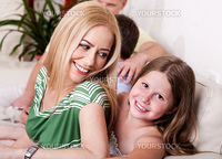 Smiling young girl and lovely mom in living room